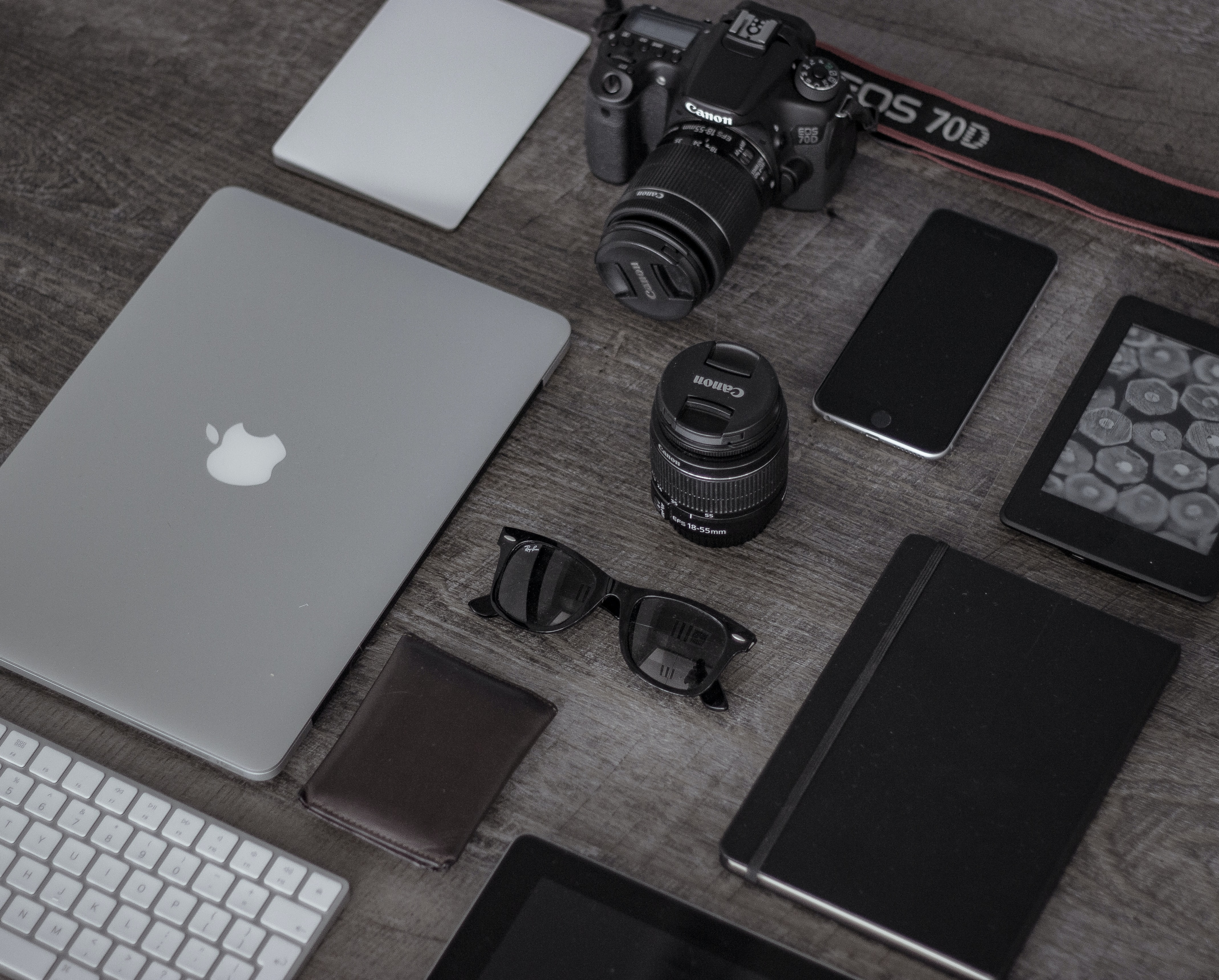 photo of a few electronics on a surface: a macbook, sunglasses, an SLR camera, an iphone, a kindle, and a notebook